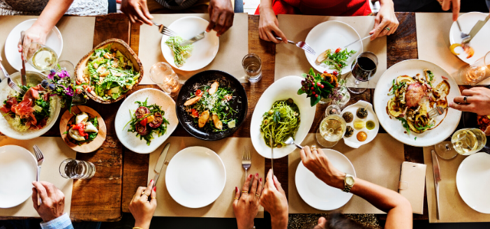 Freizeit: Gedeckter Tisch im Restaurant. Personen Essen verschiedene Speisen.